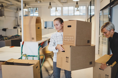 Businesswomen moving cardboard boxes into new officeの写真素材 [FYI02147298]