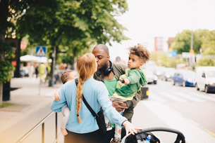 Parents kissing while carrying children on sidewalk in cityの写真素材 [FYI02147316]