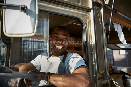 Smiling mid adult salesman looking away while driving food truck in cityの写真素材 [FYI02147325]