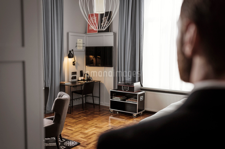 Rear view of businessman standing in hotel roomの写真素材 [FYI02147363]