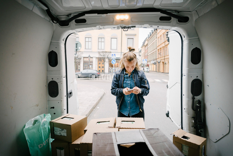 Female worker using mobile phone with cardboard boxes in delivery vanの写真素材 [FYI02147385]