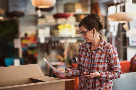 Owner reading document while listening music at storeの写真素材 [FYI02147422]