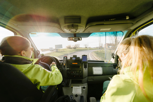 Rear view of female paramedic driving ambulance with colleagueの写真素材 [FYI02147480]
