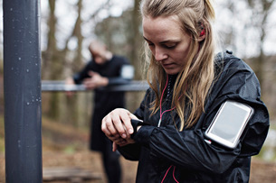 Female athlete checking smart watch at forest while man standing in backgroundの写真素材 [FYI02147495]