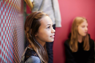 Thoughtful girl looking away with friends in background at middle schoolの写真素材 [FYI02147510]