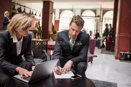 Businesswoman looking at partner signing agreement in hotel receptionの写真素材 [FYI02147515]