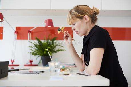 Side view of mid adult businesswoman eating lunch at table in officeの写真素材 [FYI02147561]