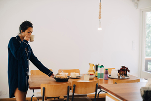Woman drinking coffee while looking at breakfast on table by wallの写真素材 [FYI02147579]