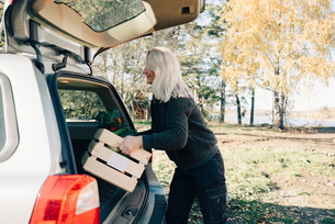 Side view of mature woman loading crate full of organic vegetables in car trunkの写真素材 [FYI02147591]