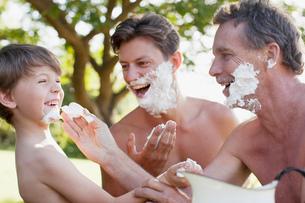 Playful multi-generation men applying shaving cream to facesの写真素材 [FYI02147601]