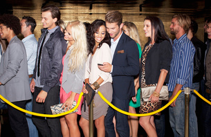 Couple with cell phone standing in queue outside nightclubの写真素材 [FYI02147625]