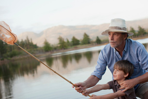 Grandfather and grandson fishing at lakeの写真素材 [FYI02147638]