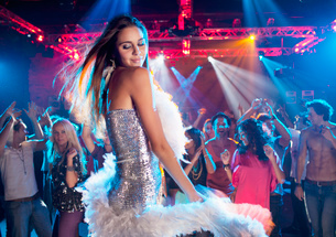 Woman in silver dress with feather boa dancing in nightclubの写真素材 [FYI02147673]