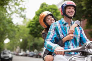 Couple riding scooter together outdoorsの写真素材 [FYI02148075]