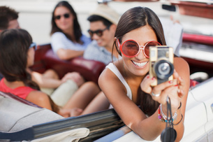 Woman taking picture from convertibleの写真素材 [FYI02148182]