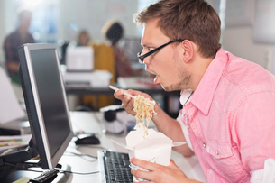 Businessman eating Chinese food at deskの写真素材 [FYI02148346]