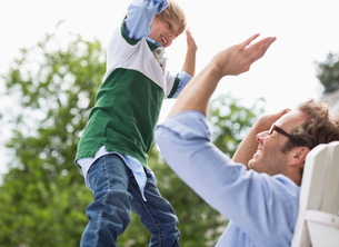 Father and son high fiving outdoorsの写真素材 [FYI02148492]