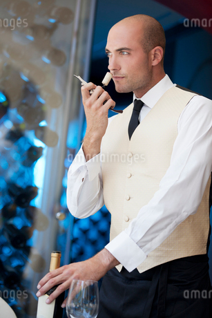 Waiter smelling wine cork in restaurantの写真素材 [FYI02148717]