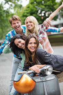 Friends smiling on scooter outdoorsの写真素材 [FYI02148811]