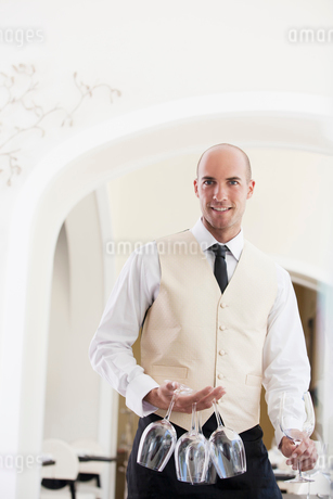 Waiter carrying wine glasses in restaurantの写真素材 [FYI02148875]