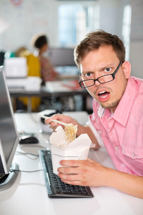 Businessman eating Chinese food at deskの写真素材 [FYI02148919]