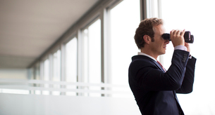 Businessman using binoculars at office windowの写真素材 [FYI02148971]