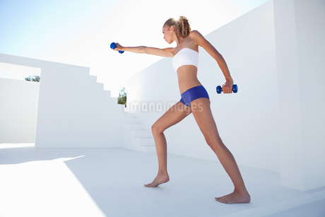 Woman lifting weights outdoorsの写真素材 [FYI02148984]