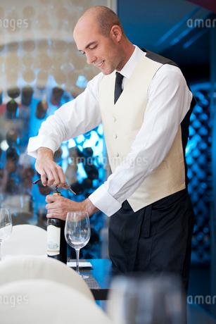 Waiter uncorking bottle of wine in restaurantの写真素材 [FYI02148988]