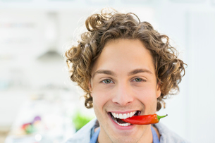 Smiling man holding chili pepper in mouthの写真素材 [FYI02149087]