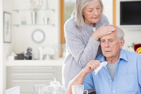 Older woman feeling sick husband's foreheadの写真素材 [FYI02149091]