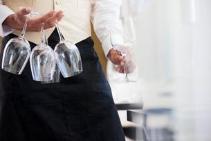 Waiter carrying wine glasses in restaurantの写真素材 [FYI02149111]