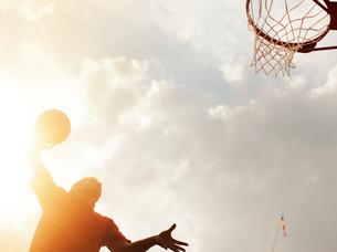 Man dunking basketball on courtの写真素材 [FYI02149134]