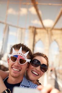 Couple in novelty sunglasses taking picture on urban bridgeの写真素材 [FYI02149148]