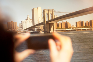 Hands taking picture of urban bridge and cityscapeの写真素材 [FYI02149176]