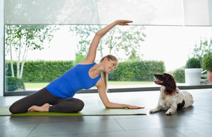 Dog sitting with woman practicing yogaの写真素材 [FYI02149197]
