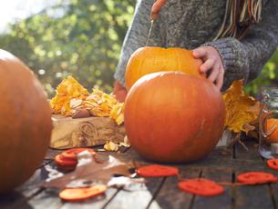 Teenage boy carving pumpkins outdoorsの写真素材 [FYI02149338]