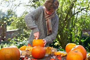 Teenage boy carving pumpkins outdoorsの写真素材 [FYI02149412]
