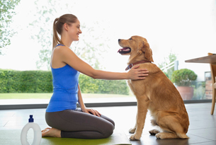 Woman practicing yoga with dog in living roomの写真素材 [FYI02149468]