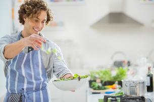 Man making salad in kitchenの写真素材 [FYI02149478]