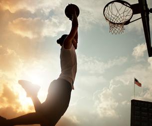 Man dunking basketball on courtの写真素材 [FYI02149600]