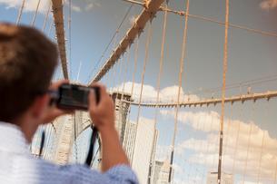 Man taking picture of urban bridgeの写真素材 [FYI02149647]