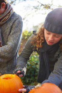 Children carving pumpkins together outdoorsの写真素材 [FYI02149690]