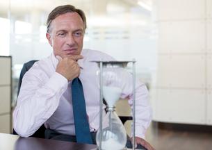 Businessman watching hourglass in officeの写真素材 [FYI02149701]
