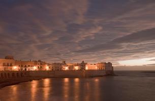 City lights reflecting in still oceanの写真素材 [FYI02149711]