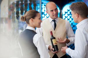 Waiters discussing bottle of wine in restaurantの写真素材 [FYI02149722]