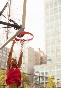 Man dunking basketball on courtの写真素材 [FYI02149845]