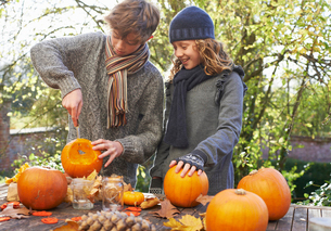 Children carving pumpkins together outdoorsの写真素材 [FYI02149924]
