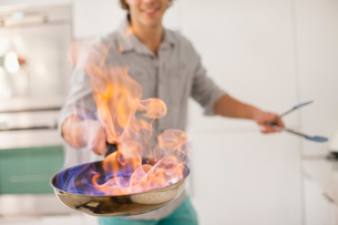 Man cooking with fire in kitchenの写真素材 [FYI02149927]