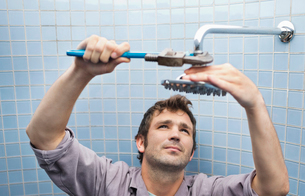 Plumber working on shower head in bathroomの写真素材 [FYI02149962]