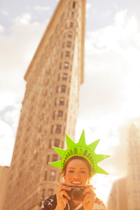 Woman in novelty hat taking picture on city streetの写真素材 [FYI02149985]